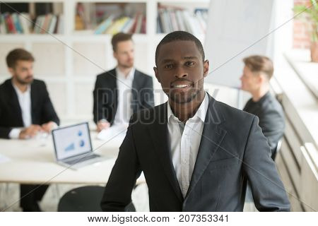 Headshot portrait of handsome young smiling african american businessman looking at camera. Blurry team of male businessmen on background, Friendly male executive, CEO, corporate worker or manager.