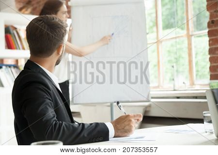 Young businessman looking at workflow chart on board, taking notes. Female project manager showing new corporate plan. Employee training, business briefing, company meeting concept. Rear close up view