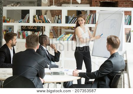 Female executive points at board with chart, training group of corporate employees during briefing. Businesswoman consulting colleagues about new workflow plan. Team listening to CEO instructions.