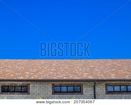 The House Is Made Of Beige Bricks, The Roof Is Covered With Bitumen Shingles. Metal Plastic Windows