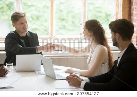 Young male executive in formal suit shaking hands with attractive female coworker. Employees greeting each other before corporate meeting, briefing about to start. Team member introduction concept.