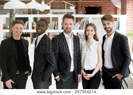 Corporate team of young smiling business people looking at camera. Multi ethnic group portrait of young entrepreneurs at workplace, friendly company representatives, executive workers and managers .