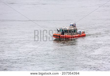 NEW YORK USA - Sep 18 2017: US Coast Guard patrol boat with officer manning gun on the bow patrolling East River during the 72th session of the UN General Assembly in New York City