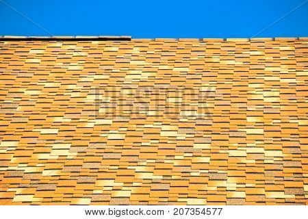 Roof From Multi-colored Bituminous Shingles. Patterned Bitumen Shingles.