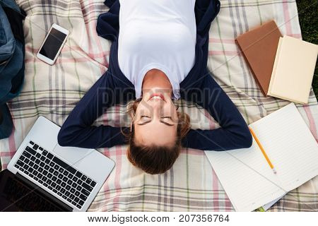 Top view of a pretty young student girl resting while lying on blanket with laptop computer and textbooks outdoors