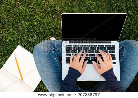 Top view of female hands typing on blank screen laptop computer while sitting on the grass with a textbook
