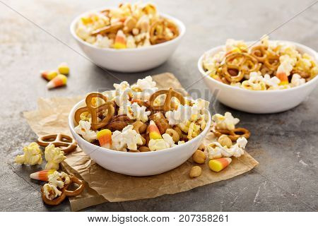 Homemade Halloween trail or snack mix with candycorn, popcorn, pretzels and nuts in white bowls