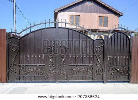 House With A Fence And Gates. View Of A New Built-up Fence And A House