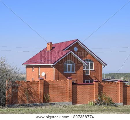 House With A Red Roof And Red Brick. Red Brick Fence. Roof Of Metal.