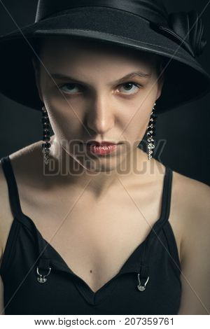 beautiful sad young woman in hat on black background