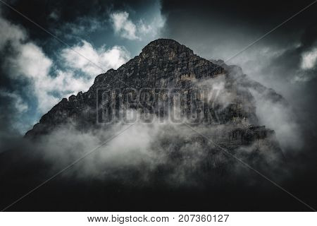 A dark, stormy fog shrouded rocky mountain peak towers above passing clouds.