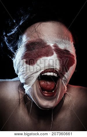 screaming crazy wounded bloody woman on black background