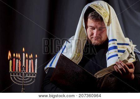Jewish Man With Beard Lighting The Candles Of A Menorah