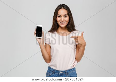 Portrait of a joyful smiling asian woman pointing finger at blank screen mobile phone and looking at camera isolated over white background