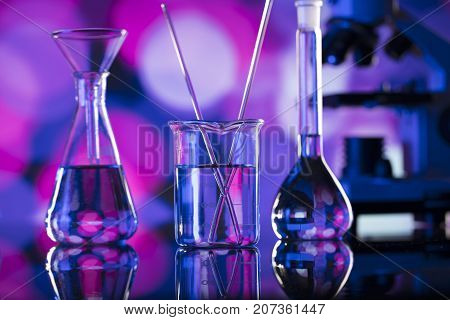 Laboratory concept. Beakers and microscope. Coloful bokeh background.