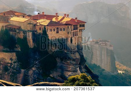Breathtaking view of Meteora Roussanou Monastery at sunset, Greece. Geological formations of big rocks with Monasteries  on top of them.