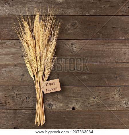 Bundle Of Wheat With Happy Harvest Gift Tag Over A Rustic Wood Background