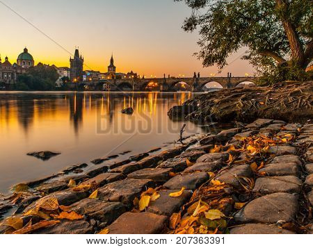 Charles Bridge with Old Town Bridge Tower reflected in Vltava River at morning sunrise time, Prague, Czech Republic.