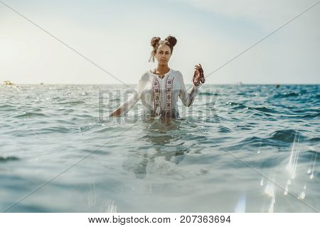 Charming young black curly lady in traditional African chemise standing up to the waist in teal seawater and holding beads in her left hand strong reflection in the bottom ripples on water surface
