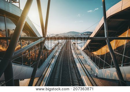 Wide-angle view from top through metallic beams of two empty railway tracks on city public railroad station with overhead passages on both sides stretching into distance; sunny evening with clear sky