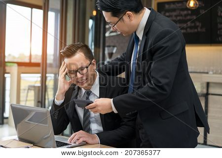 Businessmen with glasses together serious problem fail tired hard project of daily sale report with laptop computer.