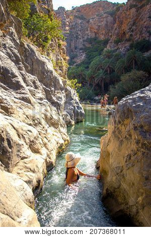 Woman passes a small waterfall of Kourtaliotis river and canyon near Preveli beach at Libyan sea, river and palm forest, southern Crete, Greece on August 27, 2017
