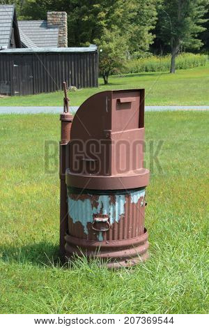 Anchored trash can in a park with a bear proof top, vertical aspect