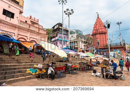 VARANASI INDIA - MARCH 14 2016: Horizontal picture of the stairs and houses at Dashashwamedh Ghat in front of Ganges River in the city of Varanasi in India