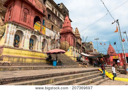 VARANASI INDIA - MARCH 14 2016: Horizontal picture of the stairs and small temple at Dashashwamedh Ghat in front of Ganges River in the city of Varanasi in India