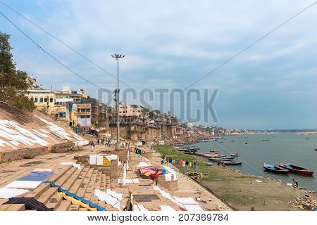 VARANASI INDIA - MARCH 14 2016: Wide angle picture of the stairs with cloths getting dry in front of the holy Ganges River with many boats in the city of Varanasi in India