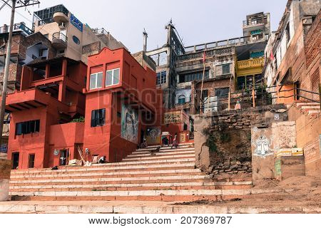 VARANASI INDIA - MARCH 14 2016: Horizontal picture of red house and stair at Narad Ghat in front of Ganges River in the city of Varanasi in India
