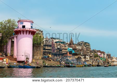 VARANASI INDIA - MARCH 14 2016: Horizontal picture of riverbank with Manikarnika Ghat with many boats in Ganges River during day time in Varanasi India.