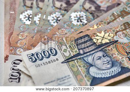 Several colorful banknotes of Icelandic krona. 5000 banknote lies on the few 1000 banknotes. Horizontal macro photo.