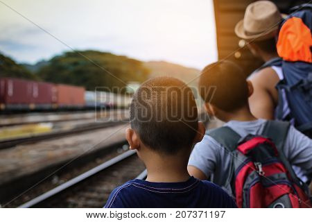 Father and sons  backpack waiting train at train station in Thailand.Back of travelers.