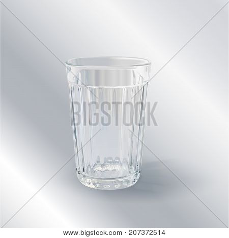 one transparent empty faceted glass on a gray background