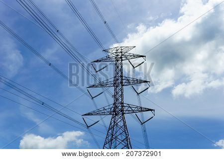 high voltage electricity pylon and transmission line with beautiful blue sky and cloud in sunny day