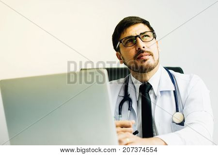 Doctor in a lab coat holding a stethoscope for patient examination.