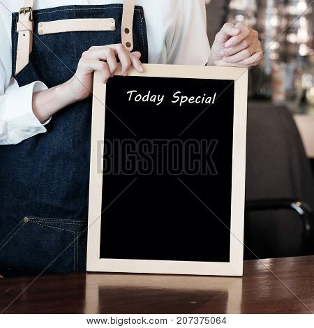 Woman hand holding blank Today special board over blur cafe background copy space for text food and drinks background