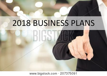 Businesswoman hand touching 2018 business plans button over blur office background banner with copy space annual plan for success in business