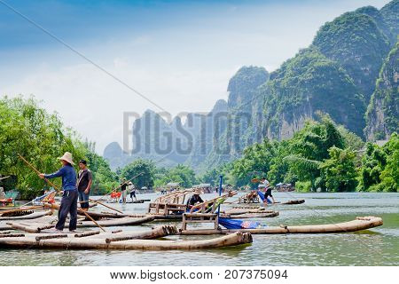yulong river china July 2011: In July tourists travel on these bamboo rafts on the yulong river to admire the karst peaks covered with dense vegetation during an exciting water tour