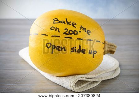 Ripe spaghetti squash with written cooking instruction on wooden table