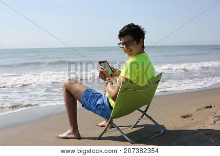 Young Boy Reads A Technological E-book At The Seaside