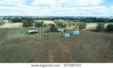 Aerial view of agricultural farm sheds and hay storage bays on farmland with eucalyptus gum trees, New South Wales, Australia