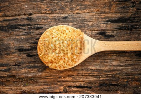 Brown sugar close-up on wooden spoon with Sugar cane