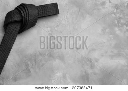 Black karate belt on grey background