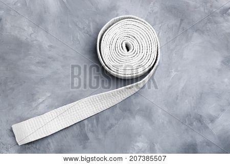 White karate belt on grey background