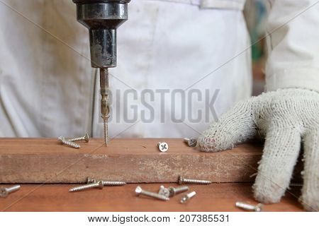 Selective focus on screws with electric tool working with hands of carpenter in white uniform in wood workshop.