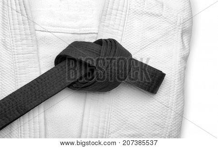 Karate uniform with black belt on white background, closeup