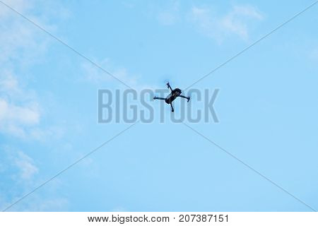 Modern drone hovering in blue sky