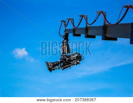 Professional camcorder on a crane against a blue sky. technology